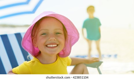 child close up portrait happy smile summer camp sitting chair umbrella backlight shallow depth of field stylized
