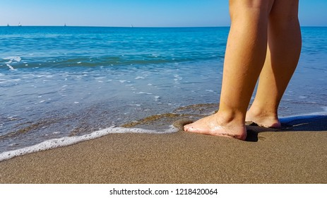 Child close to the sea with the feet in to the water