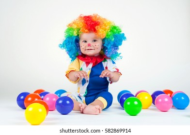 Child clown with a red nose multicolored wig in with balls
