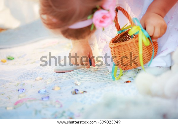 The child collecting colored clear stones to  basket. Festively decorated Easter basket in the girl's hands. Easter background. Soft focus