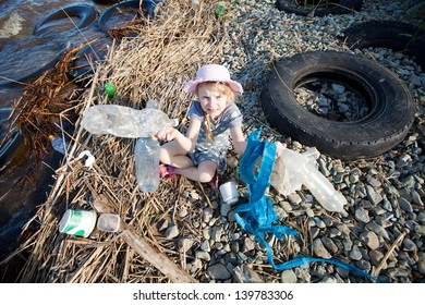 child collecting rubbish on the bank of river
