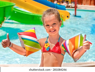 Child with colored armbands playing in swimming pool. Summer outdoor.