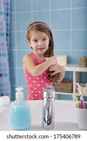 Child comb her hair in the bathroom
