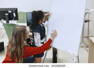 Child in computer science class. African girl standing near school board for presentation. Teacher with her student.