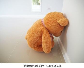 Child concept of sorrow. Teddy bear sitting leaning against the wall of the house alone, look sad and disappointed.