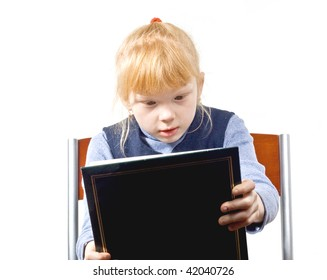 The child considers the book - a family album isolated on a white background
