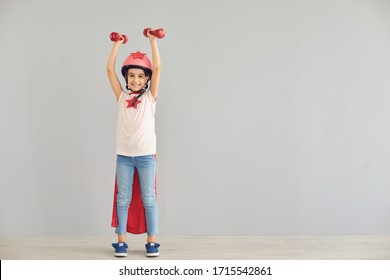 A child in a costume of a super hero raised his hands up with dumbbells on a gray background.