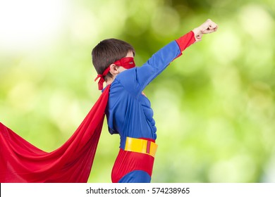 child with costume of superhero and the arm up