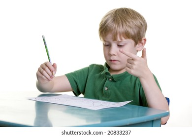 A child counts on his fingers as he works on his math homework.