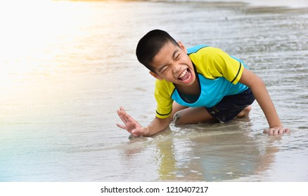 Child crawls on the beach. Happy disabled child concept.