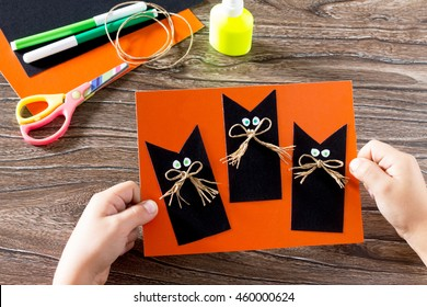 The child create a greeting card Halloween black cat out of paper. Glue, scissors, leaves velvet paper on a wooden table. Children's art project, a craft for children.