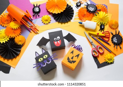 The child creates a gift box of a black cat,bat and pumpkin. A party for Halloween. Children's hands make a master class. Craft for kids. Materials for creativity of orange, purple and black colors.