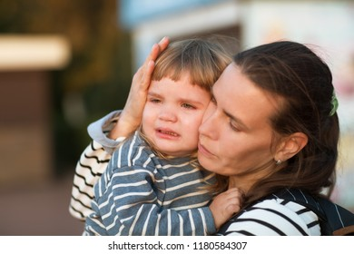 the child cries on hands at mother on walk