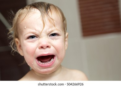 Child crying in the bath at home