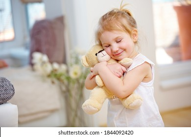 Child cuddles with her soft cuddly toy at home