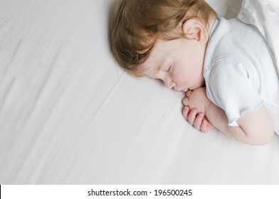 A child curled up on it's side sleeping.