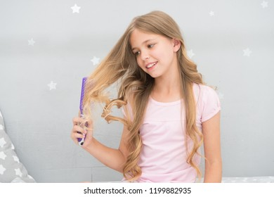 Child curly hairstyle hold hairbrush or comb. Apply oil before combing hair. Healthy hair. Conditioner or mask organic oil comb hair. Beauty salon tips. Girl long curly hair grey interior background.