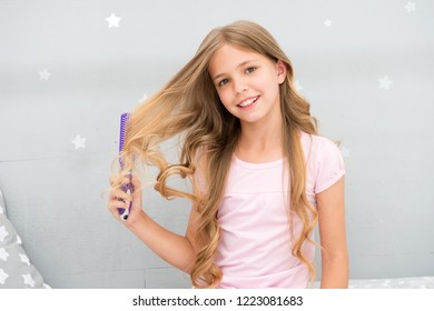 Child curly hairstyle hold hairbrush or comb. Comb hair before go to sleep. Hairdressing habits concept. Conditioner or mask organic oil comb hair. Girl long curly hair bedroom interior background.