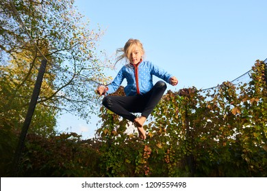 Child cute blond girl playing and jumping on trampoline with greenery background. Children are at a high risk of injury when they jump on trampolines