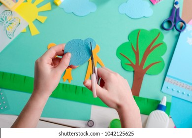 Child cuts a cloud shape from blue paper. Nature themed collage, art lesson in kindergarten.