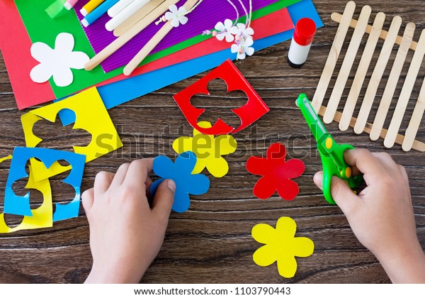A child is cutting details of a gift of summer flowers on a wooden sticks fence. Handmade. Project of children's creativity, handicrafts, crafts for kids.