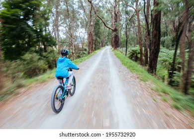 A child cycles at speed in Mt Evelyn on the popular Lilydale to Warburton Rail Trail on a warm autumn day in Victoria, Australia