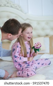 Child with dad fool around on bed, Dad tickles daughter. Young happy family together. Woman with long black hair, brown man and daughter blonde European appearance against a white interior. The