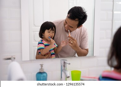 child with dad learn how to brush your own teeth on daily routine before bed