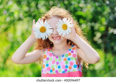 Child with daisy eyes with rainbow dress, on green bokeh background in a summer park.