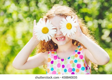 Child with daisy on green bokeh background in a summer park.