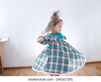 Child dancing at home. domestic kid in green dress whirling skirt
