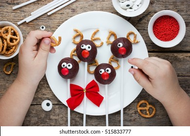 Child decorate festive reindeer cake pops cookies and candy, homemade Christmas treat for kids