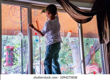child decorates a window for halloween, with colorful window markers
