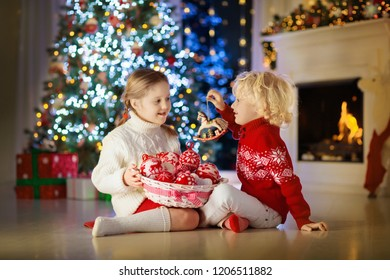 9ab2bafe5 Child decorating Christmas tree at home. Little boy and girl in knitted  sweater with handmade