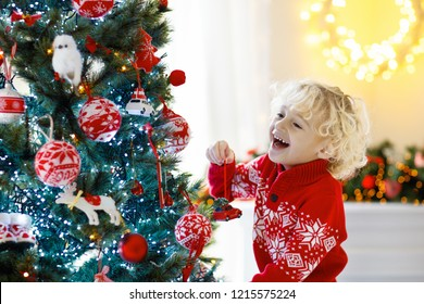 Child decorating Christmas tree at home. Little boy in knitted sweater with Xmas ornament. Family with kids celebrate winter holidays. Kids decorate living room and fireplace for Christmas.