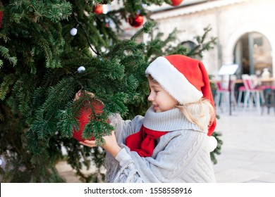 Child is decorating Christmas tree with red ornaments outside. Happy kid is enjoying holidays. Little girl in santa hat at winter market on town street. Cozy fair and New Year in Dubrovnik, Croatia.