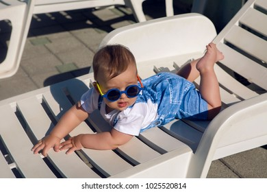 child in a denim suit and sunglasses lying on a plastic chaise longue