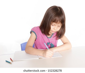Child at desk with pencils and notebook