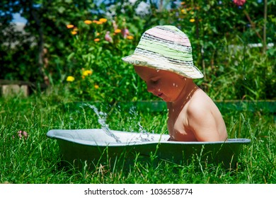 Child development in harmony with nature. Little beautiful girl playing fun with water and  taking bath outdoors on the grass in vintage washing up bowl (hygiene, happy childhood, nature concept)
