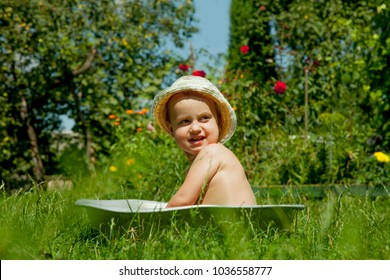 Child development in harmony with nature. Little beautiful baby girl taking bath outdoors on the grass in vintage washing up bowl (hygiene, holiday,  happy childhood, nature concept)