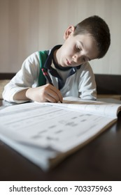 Child do his homework. Notebook for mathematic. Hand hold pen. Boy learning