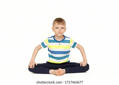 The child does gymnastic exercises for muscle stretching. Gymnastics at home during a pandemic. The boy goes in for sports Isolated on a white background.