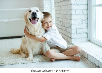 A child with a dog. Beautiful boy at home with a dog.