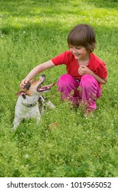 child and dog in grass