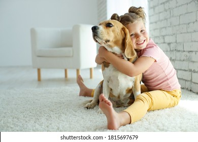 Child with a dog. Little girl plays with a dog at home. Child and animal. High quality photo.