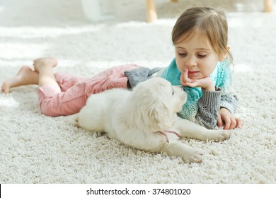 The child with the dog lying on the mat at home
