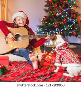 Child with a dog playing the guitar and singing near christmas tree . Merry christmas and happy New year!