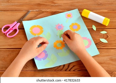 Child doing a card with flowers. Child holds a paper leaf in his hands and sticks it. Glue, scissors, greeting card on a wooden table. Paper flower craft for kids. Child art project.
