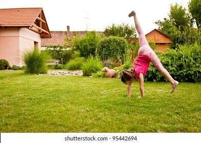 Child doing cartwheel in backyard