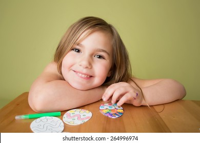 Child doing Easter activities and crafts with Easter Egg shapes, pencils and markers.